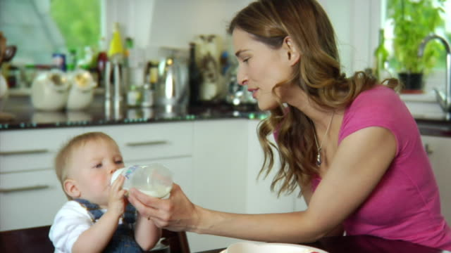 SLO MO MS Mother feeding baby boy (6-11 months) with bottle / London, United Kingdom