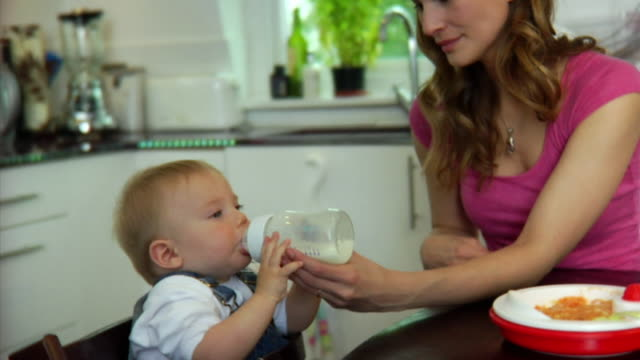 slo mo ms mother feeding baby boy (6-11 months) with bottle / london, united kingdom - see other clips from this shoot 1518 stock videos & royalty-free footage