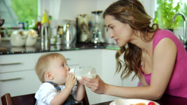 slo mo ms mother feeding baby boy (6-11 months) with bottle / london, united kingdom - biberon video stock e b–roll
