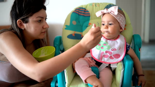 vídeos y material grabado en eventos de stock de madre alimentando bebé niña en casa - alimentar