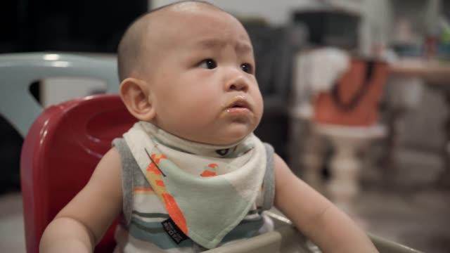 vídeos y material grabado en eventos de stock de madre alimentando a la niña en trona - 6 11 meses