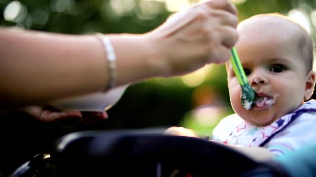 Mutter Fütterung Baby im Kinderwagen im Park