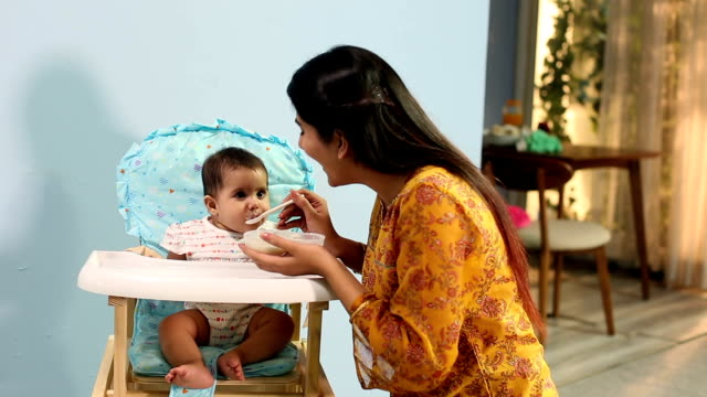 mother feeding food to her baby, delhi, india - babygro stock videos & royalty-free footage