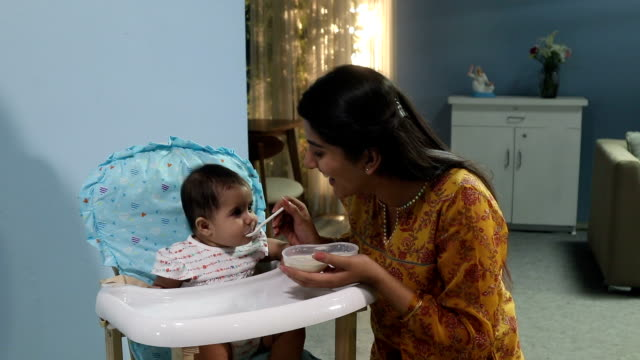 mother feeding food to her baby, delhi, india - weibliches baby stock-videos und b-roll-filmmaterial