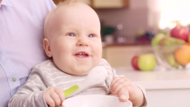 Mother Feeding Happy Baby With A Spoon