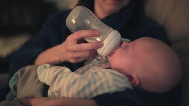 mamma utfodring hennes baby boy med mjölk flaska - mata bildbanksvideor och videomaterial från bakom kulisserna