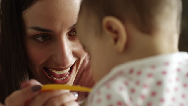 mother feeding her baby girl in kitchen - innocence videos stock videos & royalty-free footage