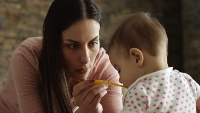 mother feeding her baby girl in kitchen - feeding stock videos & royalty-free footage