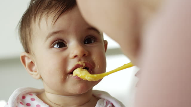 mother feeding her baby girl in kitchen - simplicity stock videos & royalty-free footage
