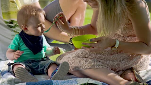 vídeos de stock, filmes e b-roll de ms mãe alimentando seu bebê ao ar livre - comida de bebê