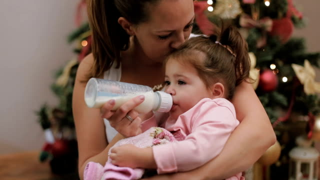 Mother feeding her cute baby girl with milk in a bottle on Christmas under the Christmas tree