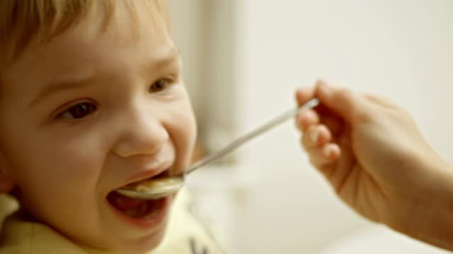 vídeos de stock, filmes e b-roll de mãe alimentando seu filho - comida de bebê