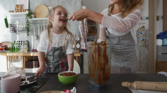 mother feeding her toddler daughter batter of a dessert they are preparing together - feeding stock videos & royalty-free footage