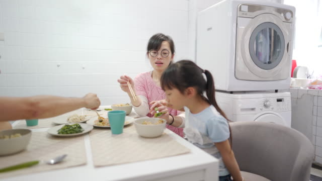 Mother feeding restless daughter in dining room