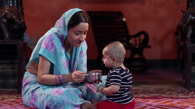 vídeos de stock, filmes e b-roll de mother feeding to her baby boy  - etnia