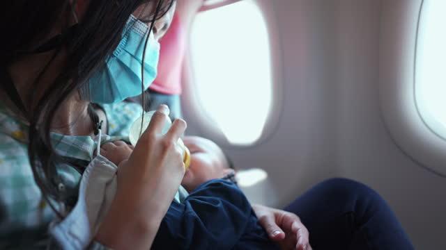 mutter ernährt ihren sohn auf reisen mit dem flugzeug. - füttern stock-videos und b-roll-filmmaterial