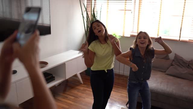 mother filming teenager daughters dancing at home - flickor bildbanksvideor och videomaterial från bakom kulisserna