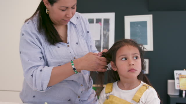 vidéos et rushes de une mère fixant ses cheveux de filles - salle attente