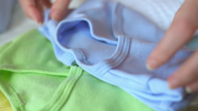 hd: mother folding baby clothes - laundry stock videos & royalty-free footage
