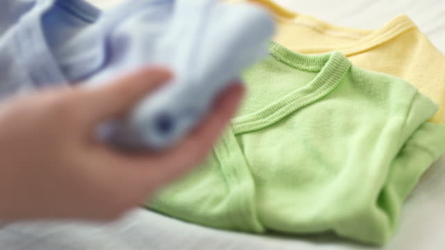 hd: mother folding baby clothes - baby clothing stock videos & royalty-free footage