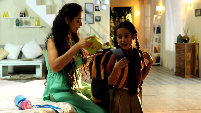mother getting her daughter ready for school, delhi, india - zaino da montagna video stock e b–roll