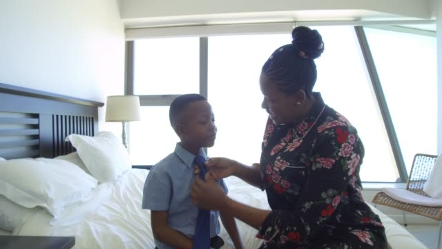 mother getting son ready for school fixing tie - son stock videos & royalty-free footage