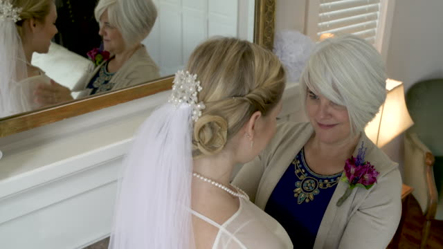 Mother gifting daughter pearl necklace on wedding day.
