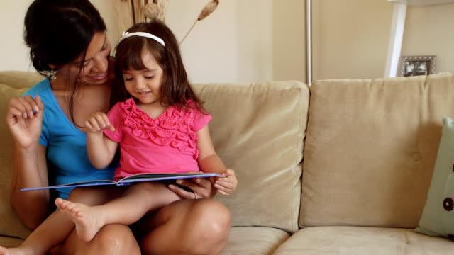 stockvideo's en b-roll-footage met mother & girl toddler make growling gestures while reading - prentenboek