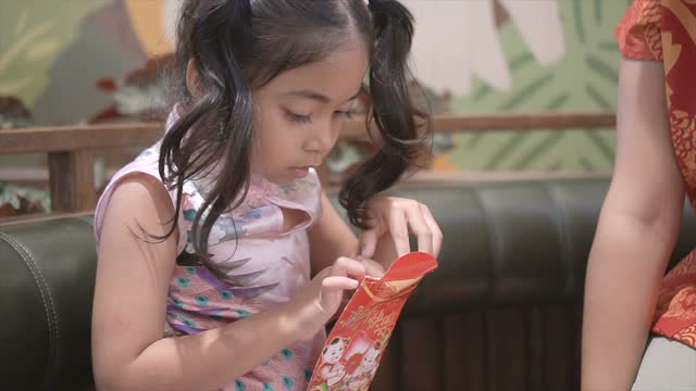 mother give the red pocket envelope to daughter in chinese new year celebrations - dress stock videos & royalty-free footage