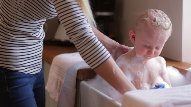mother gives baby boy a bubble bath in the sink - sink stock videos & royalty-free footage