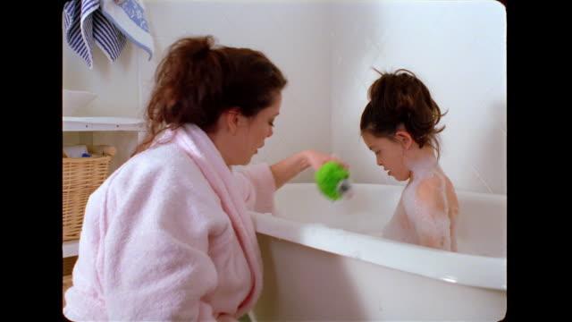 vídeos de stock e filmes b-roll de a mother gives her daughter a bubble bath. - banheira