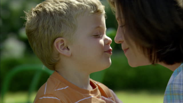 a mother gives her young son a kiss. - lips stock videos and b-roll footage