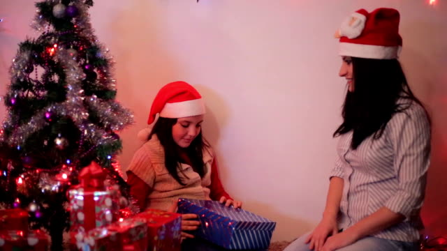 mother gives the child a gift for christmas - schoolgirl stock videos and b-roll footage