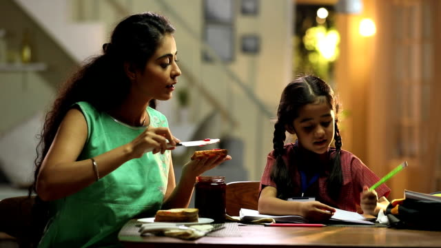 mother giving breakfast to her daughter, delhi, india - homework stock videos & royalty-free footage