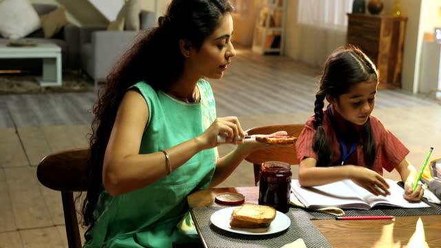 Mother giving breakfast to her daughter, Delhi, India