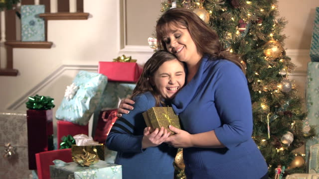 Mother giving Christmas present to daughter