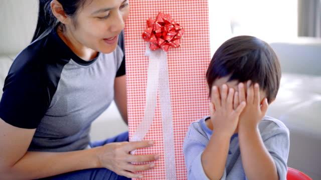 vidéos et rushes de coffret cadeau mère donnant à fils mignon. - son