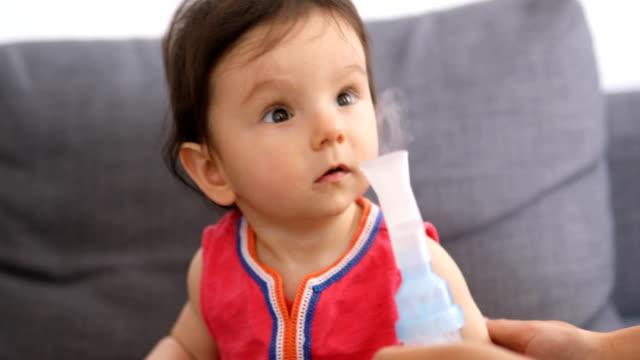 vidéos et rushes de mère qui donne son inhalation nébulisation de bébé - inhalateur
