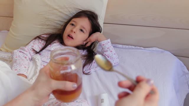 stockvideo's en b-roll-footage met moeder die honing geeft aan haar dochter in slaapkamer thuis - dubbel bed
