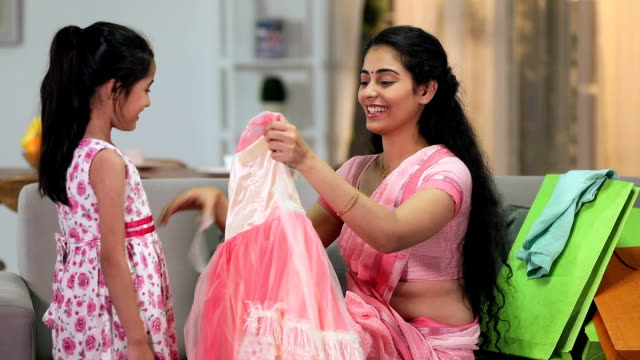 Mother giving new frock to her daughter, Delhi, India