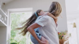 Mother Giving Smiling Daughter Piggyback Ride In Kitchen At Home