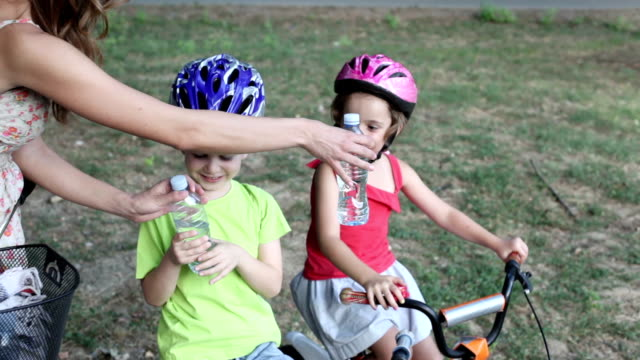 mother giving water to children riding bicycles. - cycling helmet stock videos & royalty-free footage