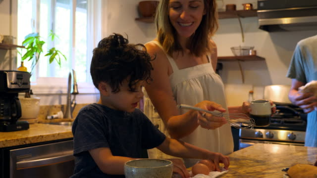 vidéos et rushes de ms mother giving young son whisk to mix eggs in bowl while making breakfast in kitchen - préparation
