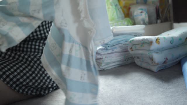 mother hand folding baby clothing concept at her home - folded stock videos & royalty-free footage