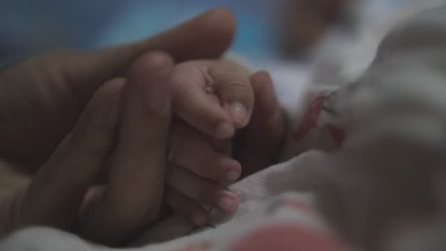 slo mo, mother hand holding hand of newborn baby - childbirth stock videos and b-roll footage