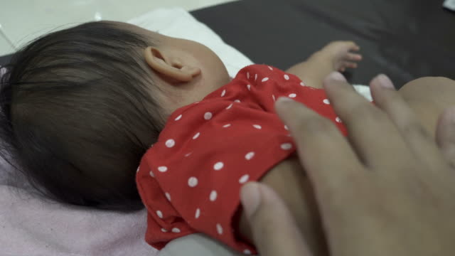 Mother hand touching a sleeping baby girl with red spots on skin. A kid is illness.