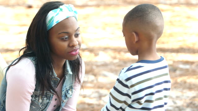 mother having serious talk with little boy on playground - single mother stock videos & royalty-free footage