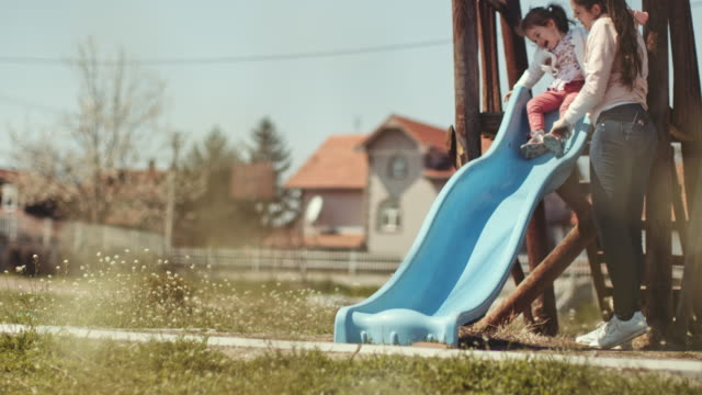 mother help her toddler daughter to slide down in playground. stock video - sliding stock videos & royalty-free footage