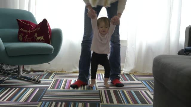 mother helping baby daughter take her first steps. - erste schritte stock-videos und b-roll-filmmaterial