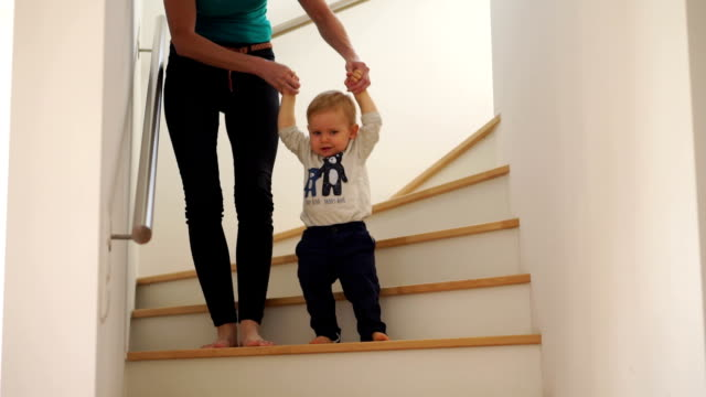 mother helping baby son down stairs